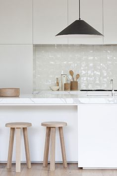 glossy tiles + white cabinetry + black pendant + wood stools + marble countertop