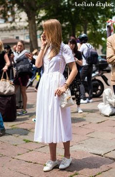 Womenswear Street Style by Ángel Robles. Fashion Photography from Milan Fashion Week. Vintage inspired midi white summer dress with sneakers and a small white and gold bag. Total white outfit spotted at Gucci fashion show, Milano.