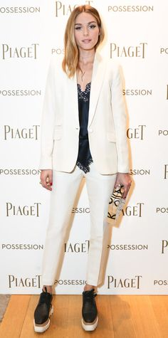 Olivia Palermo suited up for the Piaget Possession event, electing for crisp tailored white separates with Stella McCartney platform brogues and gave them an alluring, evening appeal with a satiny black lace-trimmed cami, a pale pink wraparound choker, and a graphic-print box clutch.