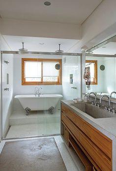 No banheiro do casal, a área molhada do boxe, com duas duchas e banheira vitoriana da IDT, é revestida com pastilhas da Vidrotil. Em frente à bancada de limestone, da Mont Blanc Mármores e Granitos, tapete feito com a mesma pedra