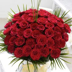 Containing 50 roses, this hand-tied is finished elegantly with fresh palm leaves.