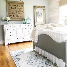 Farmhouse bedroom. White dresser, distressed wood walls, grey bed frame