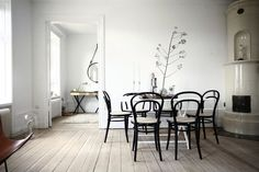 Wooden floors, black & white interior, dining table with black chairs, open spaces