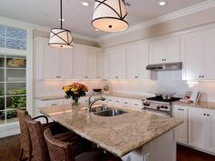 Transitional White Kitchen: A light and neutral color palette, including all-white cabinetry and beige granite countertop, make the kitchen appear bright and open. A kitchen island allows for casual seating and extra room for food preparation. From HGTVRemodels.com