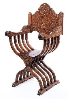 In massivem Nussholz gefertigt, in fünf Scherenstuhlspangen auf vortretenden Kufenfüßen, die Armlehnen leicht angeschweift, nach vorne hin volutiert. Die ...