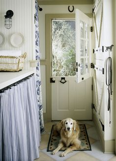 I love everything about this little side room: the dutch doors, the horse shoe over the door, the dog (except in my case it would have to be a black lab mix) laying on the rug, the counter with the curtains below, the light fixture, the barn door cabinets to the right (at least that's what I think they are?)...just adorable <3