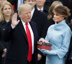 Melania Trump Photos Photos - (L-R) U.S. President Donald Trump takes the oath of office as his wife Melania Trump holds the bible on the West Front of the U.S. Capitol on January 20, 2017 in Washington, DC. In today's inauguration ceremony Donald J. Trump becomes the 45th president of the United States. - Donald Trump Is Sworn In As 45th President Of The United States