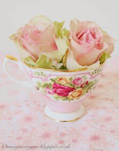An exquisitely designed rose tea cup full of real roses.  How lovely.