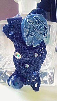 Collana corta lavorata a mano con il crochet. Vi è applicata una rosa di tessuto jeans ,pietre e perline di recupero. Da www.ideacreazioni.com