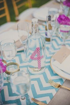 Blue chevron table runner with pink chevron tape on water jug for table numbers.