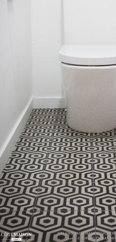Des toilettes avec sol en carreaux de ciment.