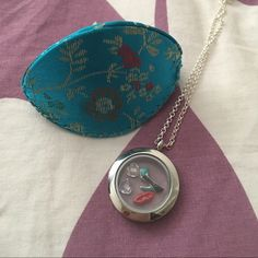 Origami owl necklace with charms Origami Owl necklace with charms  BRAND NEW, NEVER WORN! Comes with box/pouch as shown.   This beautiful necklace comes with 4 adorable charms. Charms are: red lips, high heel, 2 hearts.   This is definitely a great statement piece. Origami owl Jewelry Necklaces