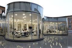 Biblioteca di Maranello. Lo studio di architettura Andrea Maffei Architects, in collaborazione con quello giapponese Arata Isozaki, ha realizzato la nuova biblioteca di Maranello. Gli interni bianchi, le pareti ondulate in vetro, il verde esterno e l'acqua intorno rendono la biblioteca un luogo ideale per immergersi completamente nella lettura. Via designtaxi.com
