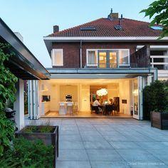 Moderne aanbouw jaren 30 woning Breda. De lichte ruime moderne woonkeuken met eetgedeelte wordt afgescheiden van de woonkamer door middel van witte hardhouten harmonicadeuren. De garage is
