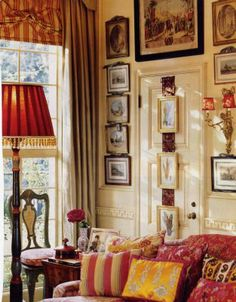 Very English looking sitting room.  Interesting idea, do you notice the artwork hanging on a broad ribbon over the door, so that it appears the whole wall is decorated with artwork.....