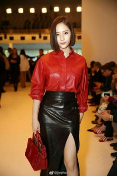 Asian girl in black leather midi skirt with slit and red leather shirt.