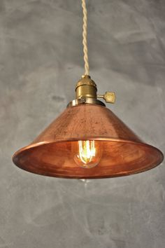 A simple, smart-looking vintage style pendant light with a weathered copper cone lamp shade. Matched with an antique style lamp socket with an aged brass finish and a flat paddle switch. Includes 7 feet of brand new cloth-wrapped twisted cord with an industrial style wall plug. (Cord color shown is antique white). The lamp shade measures 8 inches in diameter, and is constructed of solid raw copper, naturally weathered by the elements and the factory in which it is produced. We leave it…