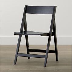 Shop Spare Black Folding Wood Dining Chair.   Designer Mark Daniel's rubberwood chair with black lacquer finish is designed to fold for easy storage.  The Spare Black Folding Dining Chair is a Crate and Barrel exclusive.