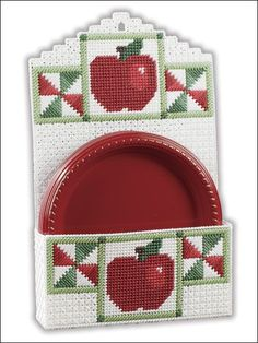"These helpful country-kitchen accessories pull double duty as warm and charming accents for your home. This e-pattern was originally published in Homespun Apple Kitchen. Size: Plate Holder: 9 3/8"" x 14 5/8"" x 2 1/8"" (23.8cm x 37.2cm x 5.4cm). Towel Holder: 9 1/4"" x 7 3/4"" (23.5cm x 19.7cm). Made with plastic canvas yarn and 7-count plastic canvas. Skill Level: Intermediate"