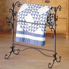 Display an heirloom quilt or keep cashmere throws on hand with this graceful quilt rack, featuring a black finish with gold highlights and 3 bars.