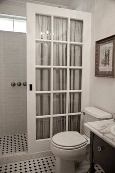 Old french pocket door used instead of an expensive glass shower enclosure.