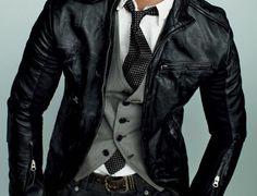black leather jacket, grey vest, white button up, black tie, jeans.