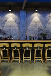 A Garage Turned Restaurant in Tasmania : Remodelista.I love this bar.the rustic wall is perfection.