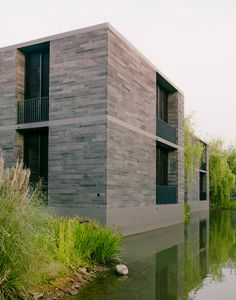 David Chipperfield has completed a series of stone apartments raised on plinths above the surface of a water garden in eastern China.