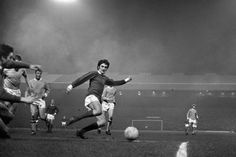 George Best, remembered as one of the greatest ever doing what he did best, as he glides past his opponents on a foggy evening in the 1960's