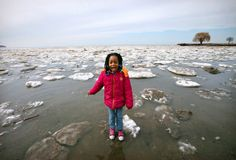 Treazure Maines, 7, a second-grader at University of Cleveland Preparatory School, stands on a tiny iceberg along the shoreline of Lake Erie after testing the pH balance of the water at Edgewater Park. For the past eight weeks, Maines and other second- and third-grade girls have participated in a Girl Scout Series called the Wonders of Water (WOW) program. The WOW program fosters environmental stewardship and engages the girls in science and math relating to the outdoors.