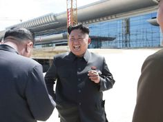KCNA picture shows North Korean leader Kim Jong Un laughing during a visit to the construction site of a terminal at Pyongyang International Airport