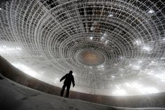 A man walks inside of the crumbling oval skeleton of the House of the Bulgarian Communist Party on mount Buzludzha in central Bulgaria on March 14, 2012.