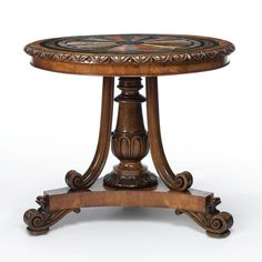 A FINE WILLIAM IV SPECIMEN MARBLE TOP OAK AND MAHOGANY CIRCULAR TABLE IN THE MANNER OF GILLOWS CIRCA 1835  the inset top with specimen marbles and fossilized stones within a slate border, the scrolled feet on casters; the inside frame with a paper label and inked illegible inscription.
