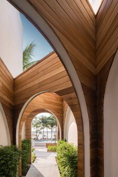 Connecting the various parts of this modern hotel are wood lined walkways that contrast the white exterior of the hotel. #Walkway #Wood #Arches