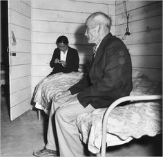 """Old Mr. Konda in barrack apartment, after supper. He lives here with his two sons, his married daughter and her husband. They share two small rooms together. His daughter is seen behind him, knitting. He has been a truck farmer and raised his family, who are also farmers, in Centerville, Alameda County, where his children were born."" -- Photographer: Lange, Dorothea -- San Bruno, California. Tanforan Civilian Assemby Center. 6/16/42 (Dorothea Lange)"