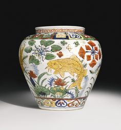 RARE WUCAI 'FISH' JAR JIAJING MARK AND PERIOD the tapering ovoid body surmounted by a short neck with lipped rim, painted to the exterior with carp swimming in a lotus pond admist aquatic plants, framed by a lappet band above and ruyi heads below, the neck encircled with a classic scroll band, the base inscribed with a six-character Jiajing mark, Japanese wood box Quantité: 2 23cm., 9 1/8 in.