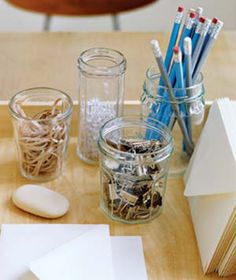 Contain Office Supplies in Glass Jars For a clean, fresh look, use clear jars (and glasses) of various heights and shapes to hold office or sewing supplies.