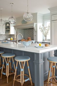 Two toned kitchen with blue island. kitchen with clear glass globe pendants over blue kitchen island with white marble countertops and sink lined with blue French cafe bar stools. Two-tone kitchen features light gray cabinets paired with black countertops and linear light gray tile backsplash. Light gray kitchen hood features pull-out spice racks flanking cooktop as well as corner open display cabinet. #Kitchen #TwotonedKitchen Kerry Hanson Design.