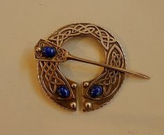 This cloak clasp by Master Ark (www.MasterArk.com) is made from cast bronze and is set with three lapis. It can be used to fasten a cloak, on a scarf, shawl or sweater, or on a kilt.