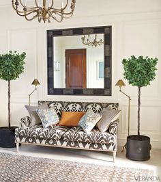 Whealon, a globe-trotter, enlists experts in far-flung places to create authentic elements. In the living room, the linen curtains' Victorian trim was embroidered onto burlap by artisans in India. He had wall lights made in Morocco for a stair landing.<br /><br /><em><strong>Jansen sofa, Amy Perlin Antiques, in Dedar ikat. Mirror, Ciancimino, and chandelier, both vintage. Antique rug, Beauvais.</strong> </em>