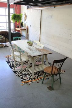 Rustic trestle table. My fave! Cute greenery and rug also.