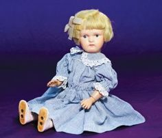 """AMERICAN CARVED WOODEN DOLL BY SCHOENHUT. Marks: Schoenhut oval sticker on back. 16 ½"""". Carved wooden socket head on spring-jointed carved wooden body, painted features, blue eyes, upper eyeliner and lashes, multi-stroked brows, open/closed mouth with painted teeth, original blonde mohair wig, original union suit, stockings and leather shoes with holes in bottom for insertion on metal stand, newer cotton dress"""