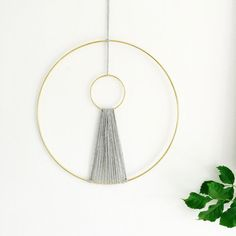 This beautiful Modern Macrame Wall Hanging is lovingly handmade in our Brighton Studio. Two Gold rings, joined together by chunky grey wool. A minimalist wall hanging with a bohemian twist. ........................................ Measurements: Width of large ring: 12 inches