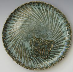 This stoneware plate has the Naragon White glaze over Blue Green glaze, fired to Cone 6 in oxidation. The butterfly area was waxed before the Naragon White glaze was applied.
