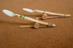 Catapult using plastic spoon, Popsicle sticks, cork, & rubber band. I added a second rubber band near the end of the spoon handle to secure the spoon better. Ask kids to experiment with the placement of the cork to see if they get more or less distance with projectiles. Let's use marshmallows or pom poms for shooting! This is one of the more frugal stick catapult designs I found, using only 2 sticks. Also, there is no gluing, so no wait time betweening making and playing.