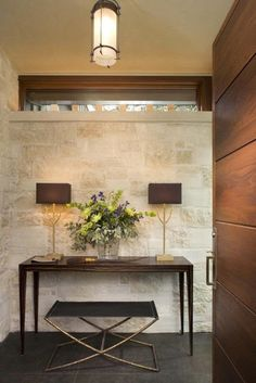 foyer console table gold lamps benches gray floor tile stone wall