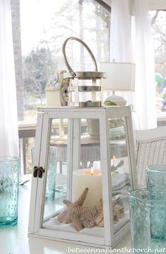 Beach Table Setting With Lighthouse Lantern Centerpiece | http://betweennapsontheporch.net/beach-themed-table-setting-tablescape-with-lighthouse-lantern-and-shell-sailboat-dishware/