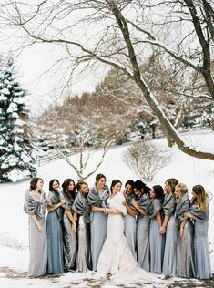 Winter wedding ideas for a modern, winter minimalist wedding party—Group of gown-clad women standing in snowy landscape