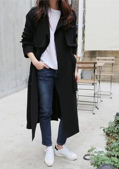 Consider wearing a black trench and navy jeans for a glam and trendy getup. A pair of white and black leather low top sneakers brings the dressed-down touch to the ensemble.   Shop this look on Lookastic: https://lookastic.com/women/looks/black-trenchcoat-white-crew-neck-t-shirt-navy-jeans/17369   — White Crew-neck T-shirt  — Black Trenchcoat  — Navy Jeans  — White and Black Leather Low Top Sneakers