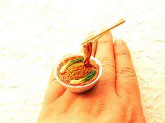 """Wo wir grade bei Ramen waren: Im Etsy Shop von SouZouCreations gibt's japanisches Essen als Ringe, oben der """"Kawaii Cute Japanese Floating Food Ring – Tantanmen – Spicy Ramen Noodle"""" (und irgendwas stimmt mit der Hand nicht, ohne dass ich sagen könnte, was). Sushi für die Finger, toll! Und ich liebe die Infotexte dazu: Sooooo cute!        This is soooo cute ring! There is a bowl of noodles with veggies and almost red color soup and chopsticks are holding up some noodles!! It is on a silver…"""